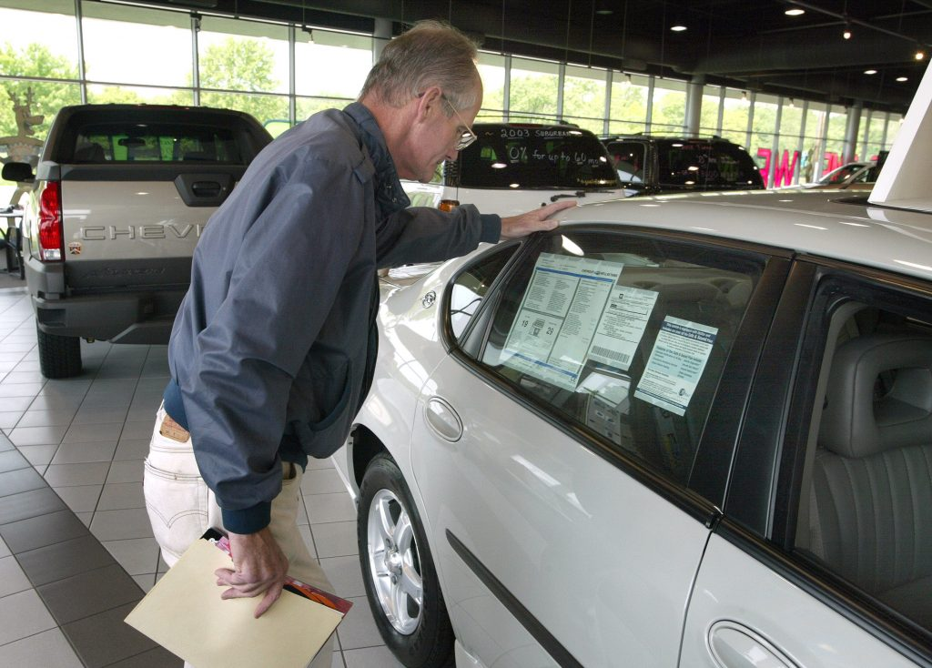 A man looks for the destination fees on the sticker of a new car at a dealership.
