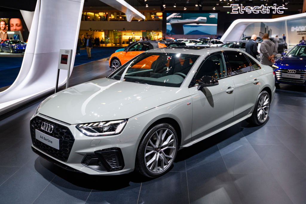The 2021 Audi A4 in Nardo Grey at an auto show, with other models in the  background.