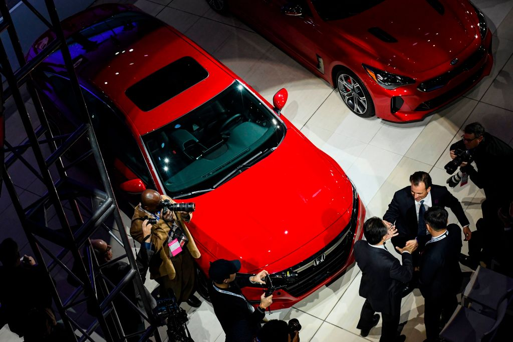 A cherry red Honda Accord with a sunroof is crowded by media at an auto show.