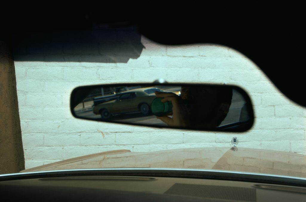 A reflection, in the rear-view mirror of a car, of a man drinking from a bottle.