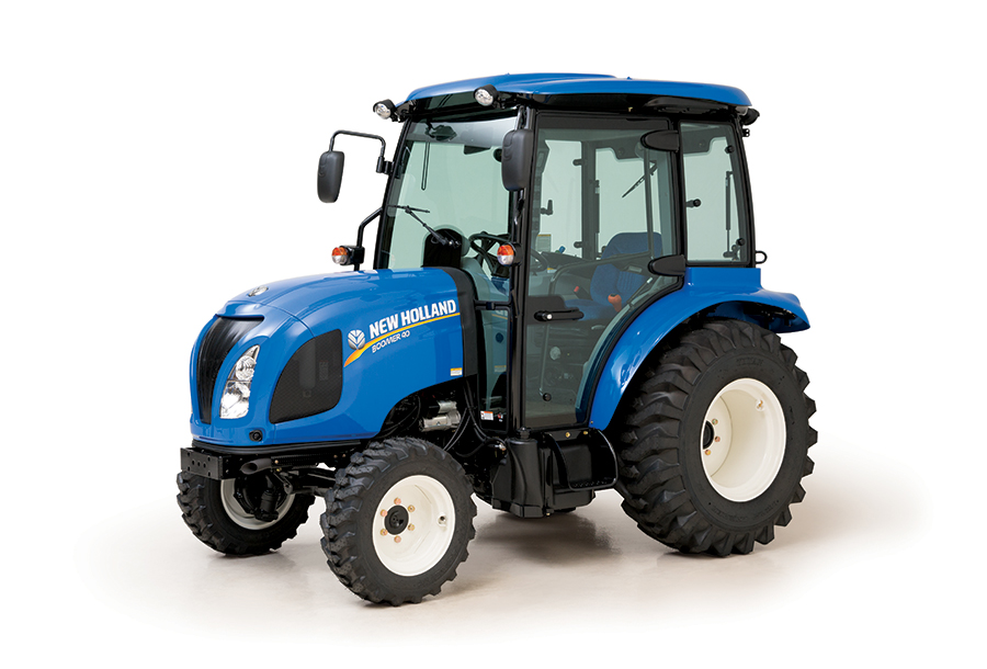a blue new holland compact tractor with a cab in a press photo against a white backdrop.