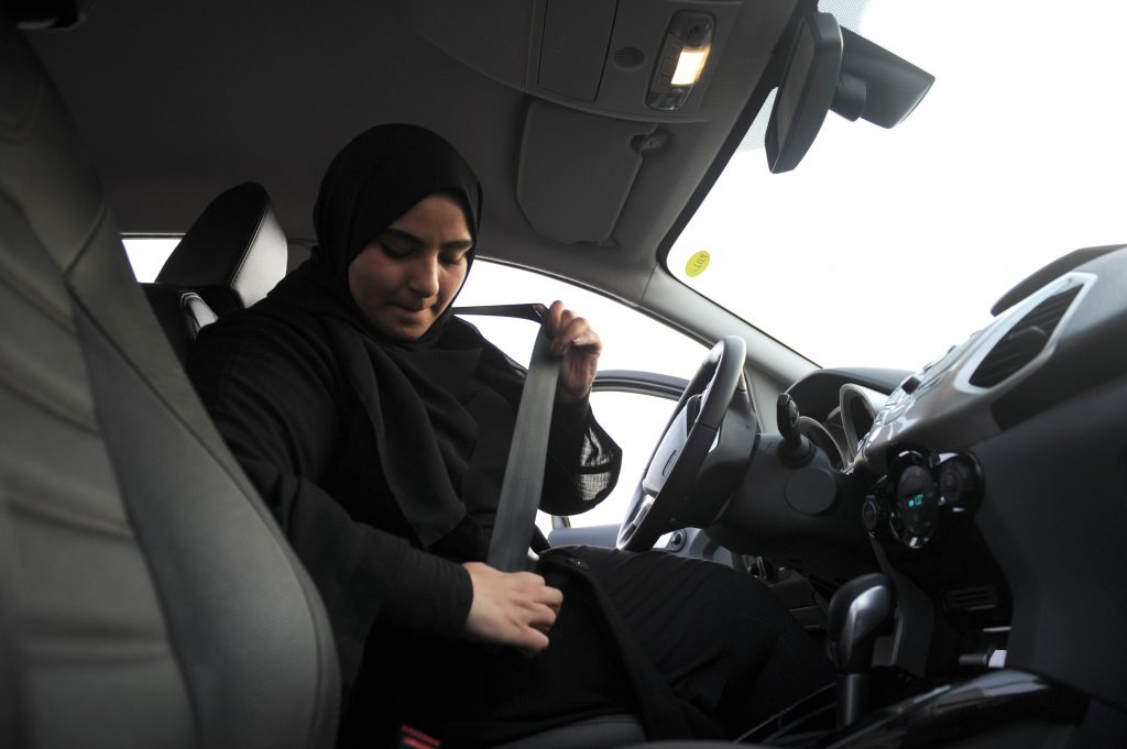 A woman buckles her seatbelt before driving