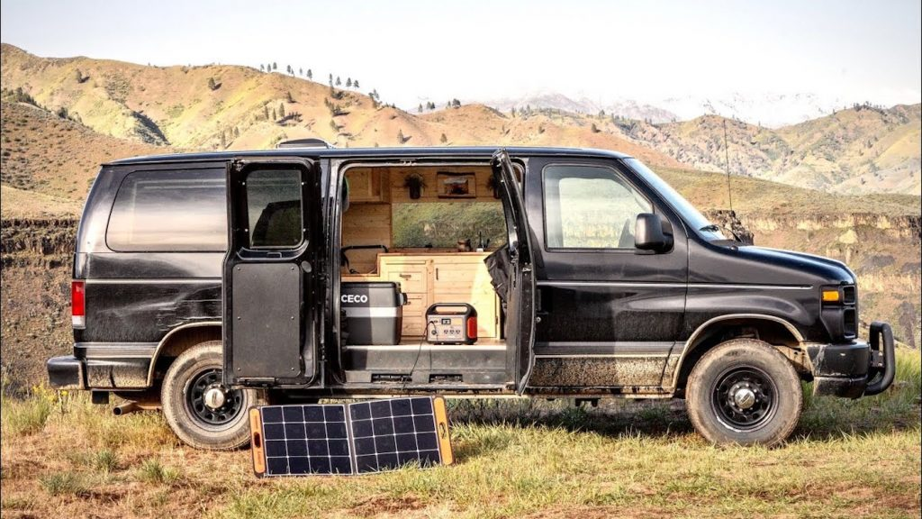 Chase Christopher's affordable camper van build is a black Ford Econoline parked in the hills