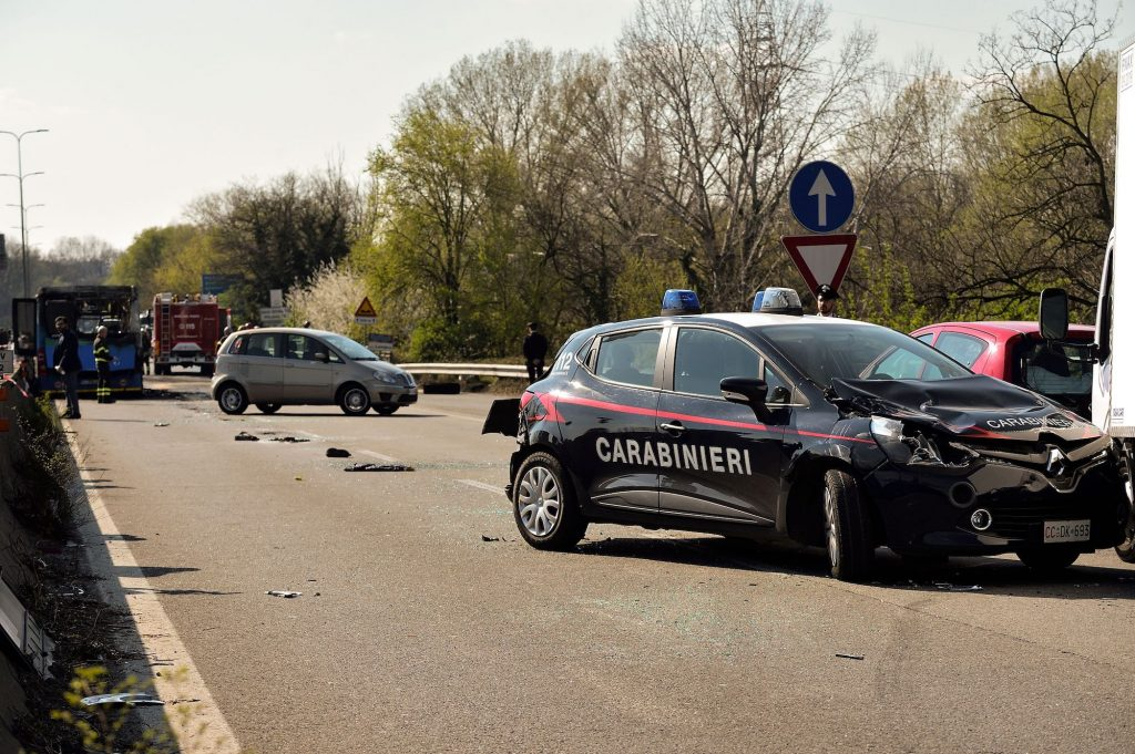 A damaged car of the Italian Carabinieri police (R) is pictured next to the wreckage of a school bus.