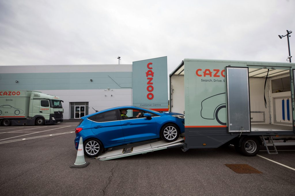 An employee drives a second-hand Ford Motor Co. Fiesta automobile onto a car transporter.
