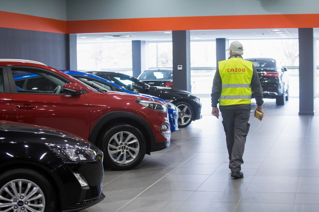An employee passes second-hand automobiles ready for delivery.