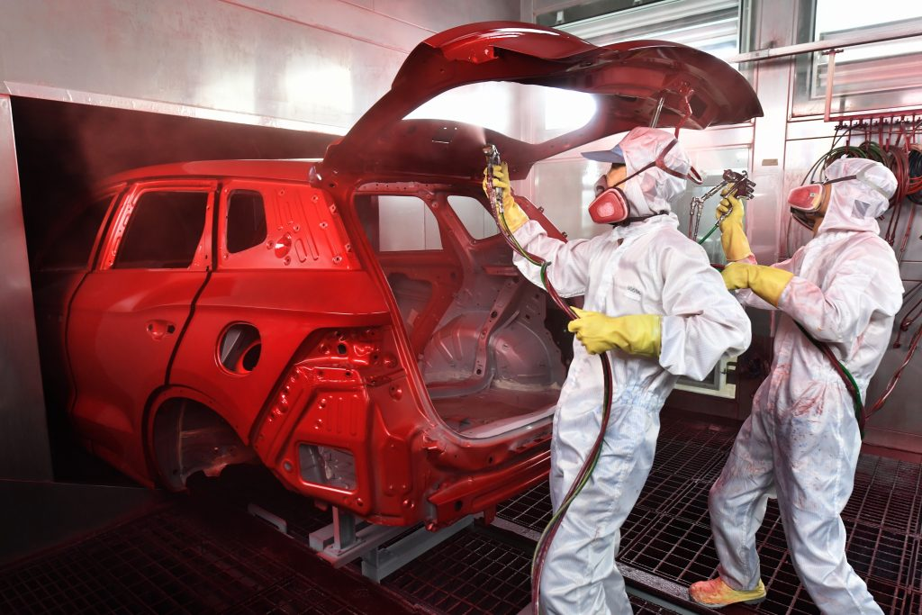 Technicians in full-body protective gear and respirators spray paint the body of a car red