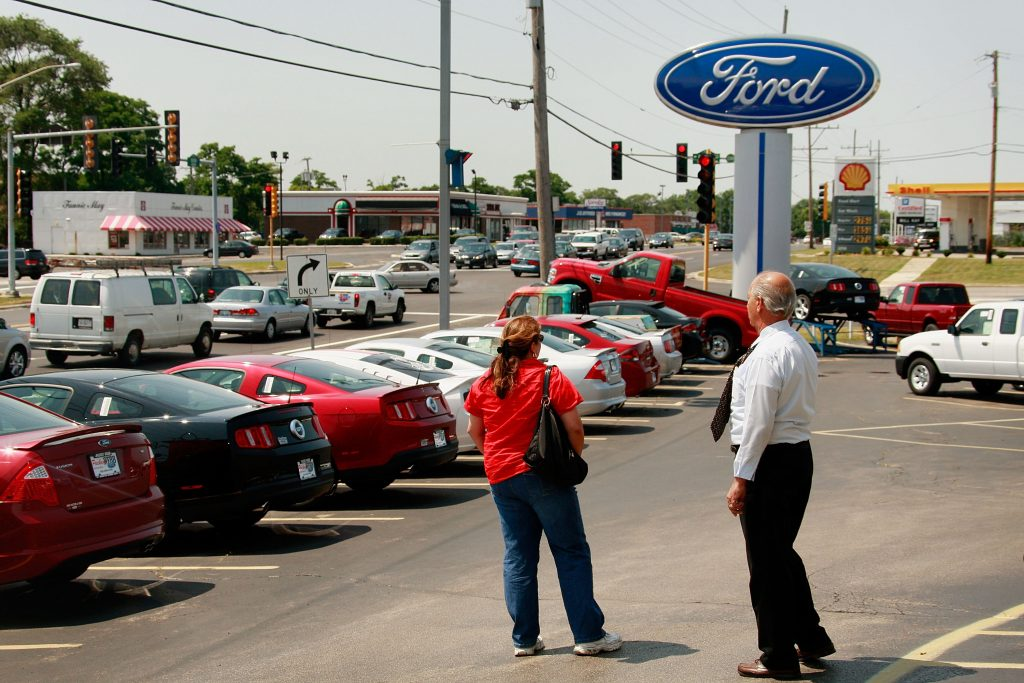 A saleman helps out a customer at a Ford dealership August 3, 2009 in Downers Grove, Illinois.