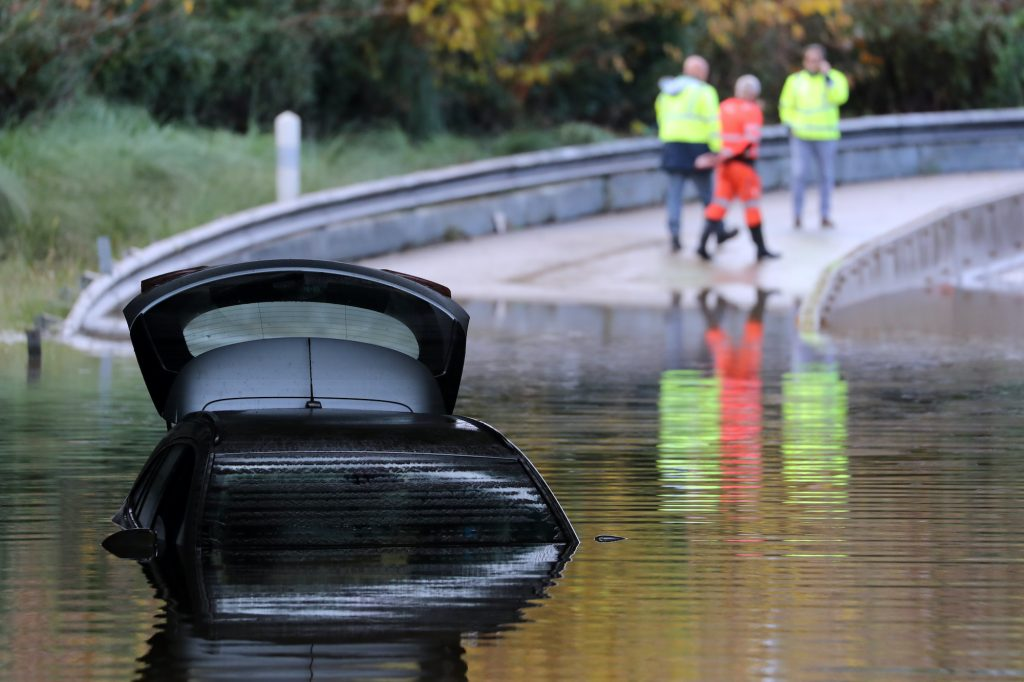 Rescuers walk by a car partially submerged in the water on a flooded road.