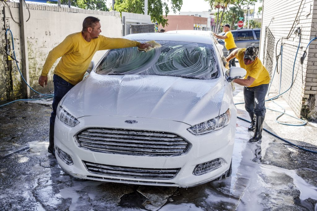 Two workers wash a car