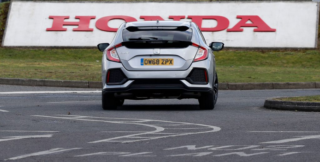 A silver honda civic rear end on the track