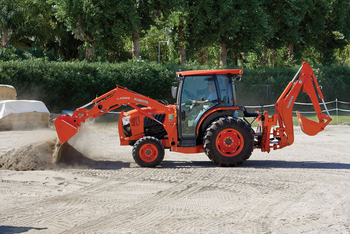 an orange Kubota compact tractor working in sand