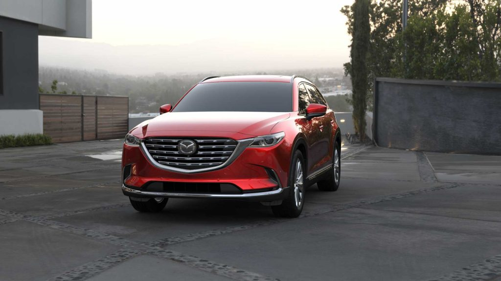 A red 2021 Mazda CX-9 parked in a drive way near a home