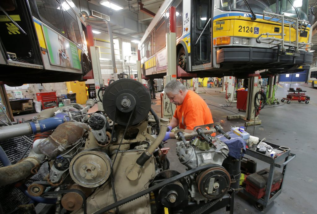 A machinist in an orange tee shirt and blue gloves rebuilds a large bus engine