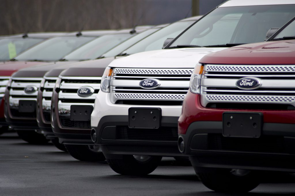 A line of multi-colored Ford Explorers in a parking lot
