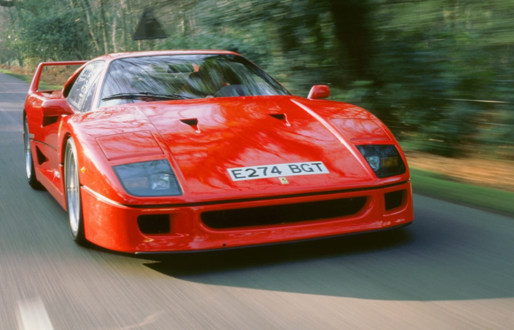 A red Ferrari F40 drives down a forested street, photographed from the nose.