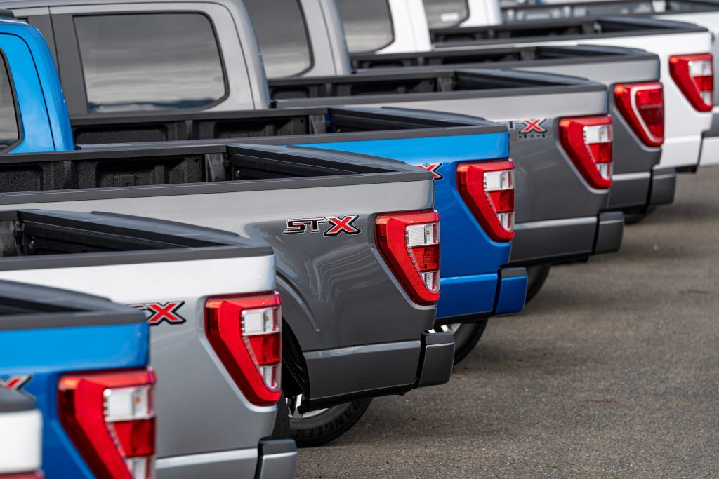 a row of 2021 Ford F-150 pickup trucks in a row on the sales lot