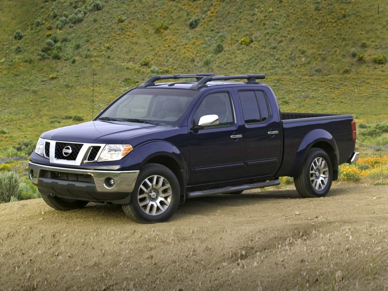 a dark blue 2021 Nissan Frontier parked in the dirt with green hills in the background
