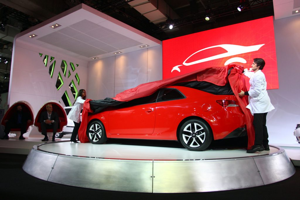 A red kia forte coupe being unveiled