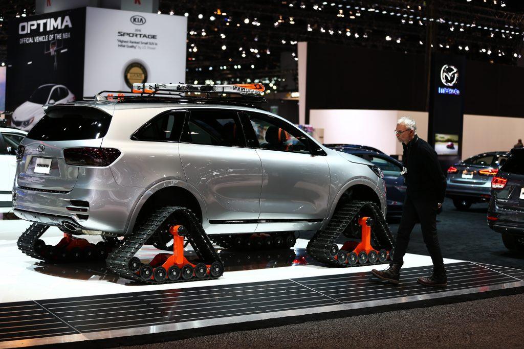 A silver Kia Sorento riding on snow tracks in an auto show booth