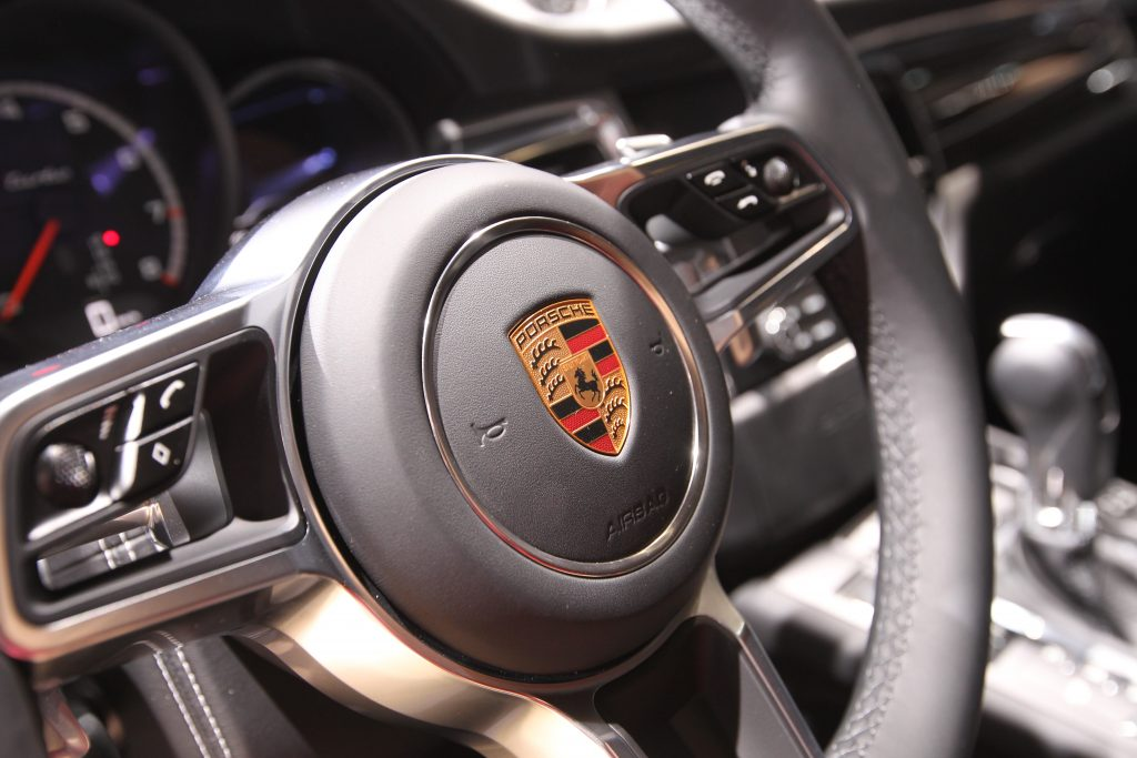 The black, leather-wrapped wheel of a Porsche Macan photographed from the exterior looking in.