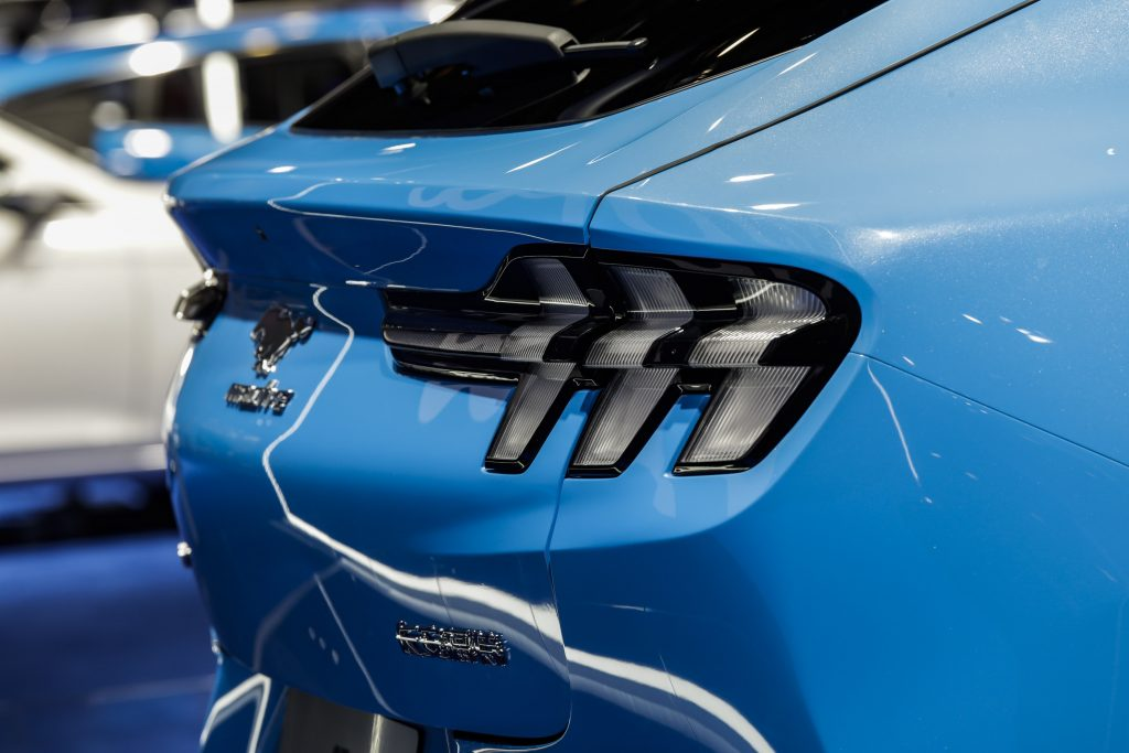 A close up of the rear end of a blue Mustang Mach-E