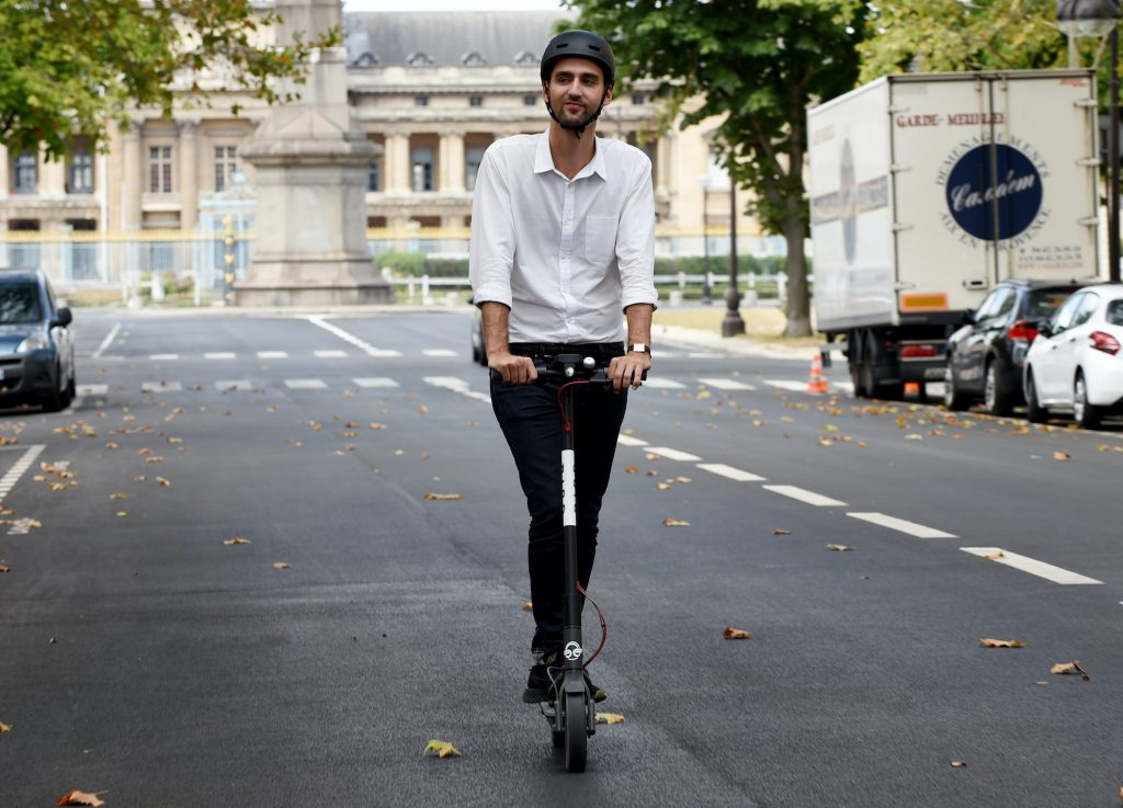 A man drives on an electric scooter in Paris.