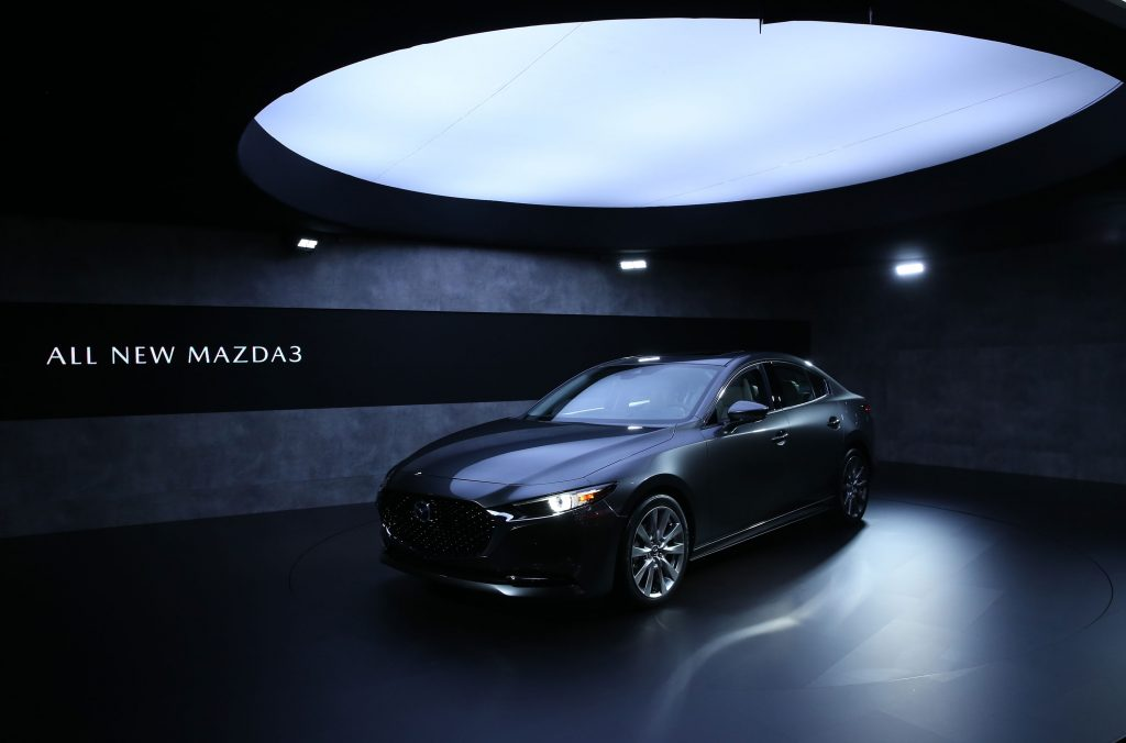 A top Consumer Reports pick, the 2020 Mazda3 in grey is shown under a light box at the L.A Auto Show