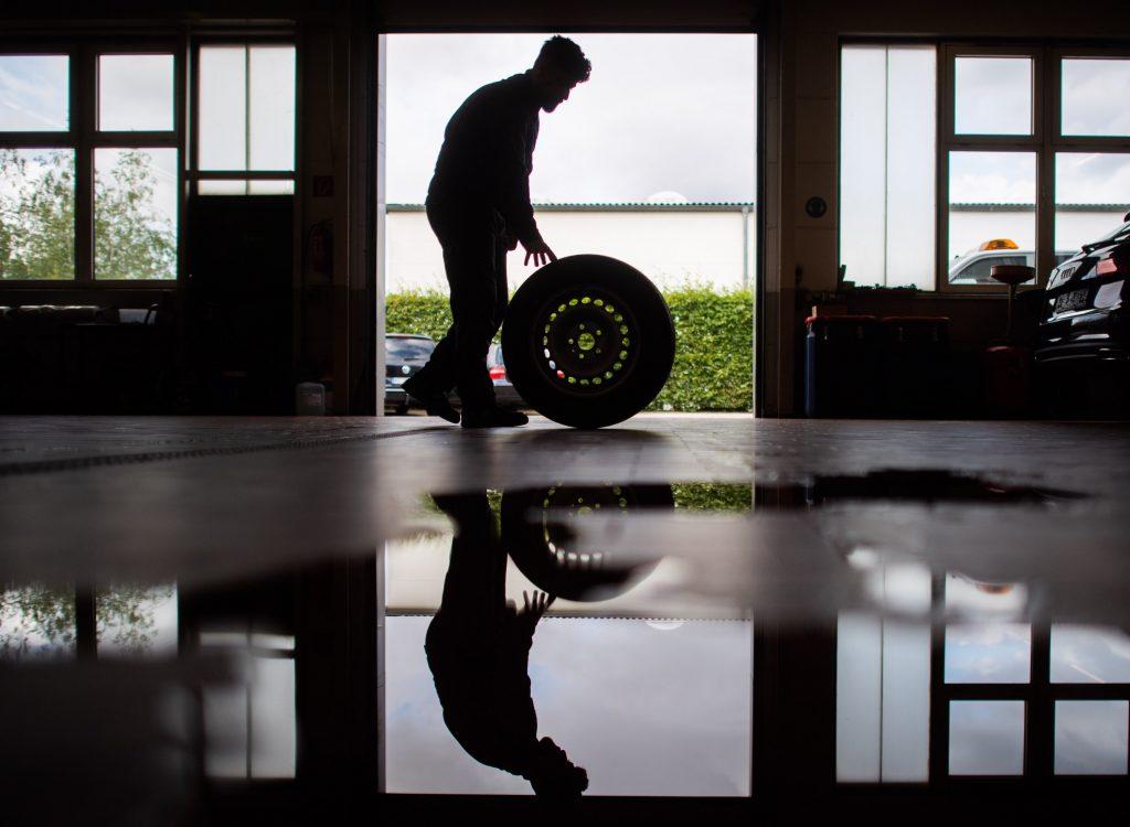 Mechanic rolling a wheel through the shop