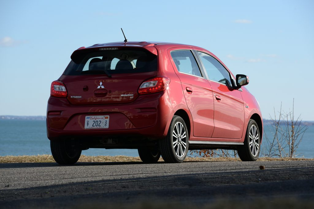 A red mitsubishi mirage parked by the water