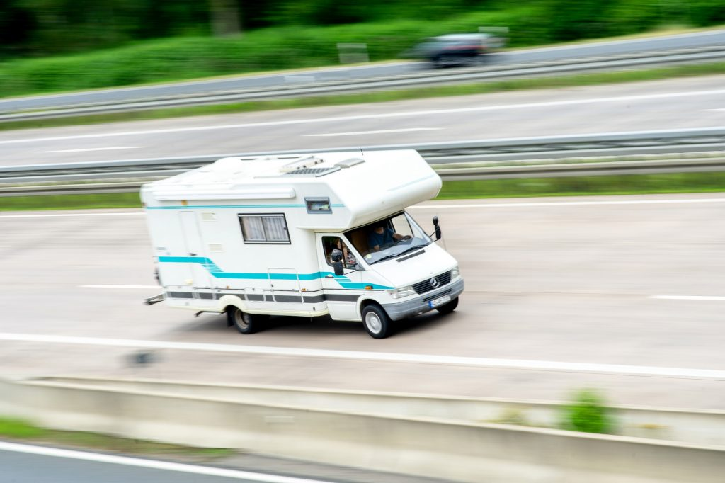 A white and turquoise-blue Mercedes-Benz RV traveling on a highway