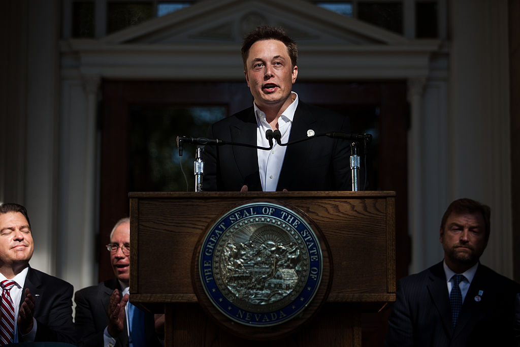 Elon Musk stands at a podium with the Nevada State Seal on it, speaking to a crowd