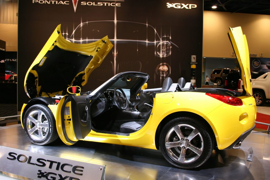 A yellow pontiac solstice GXP with the doors, trunk and front hood open