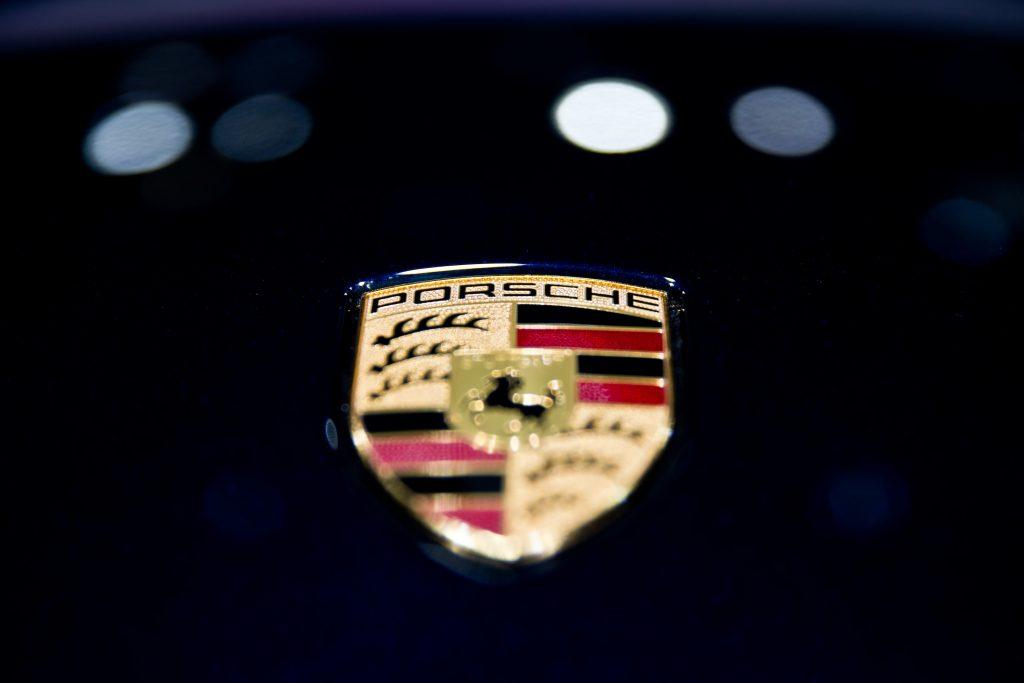 Closeup of a Porsche badge on a black car