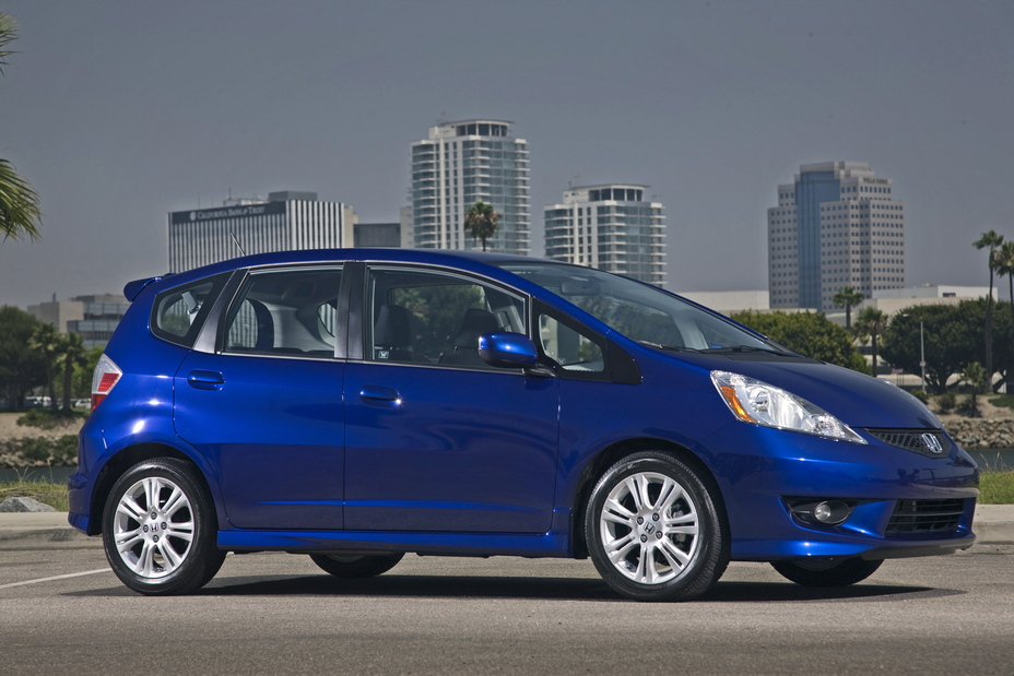 A blue 2011 Honda Fit parked outside in the city.