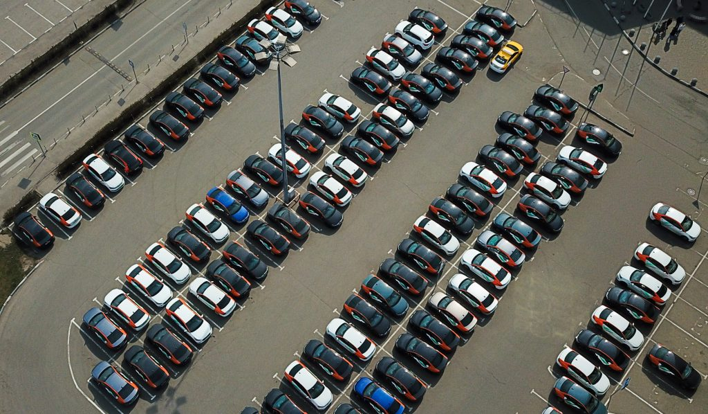 An overhead view of a parking lot full of car-sharing vehicles