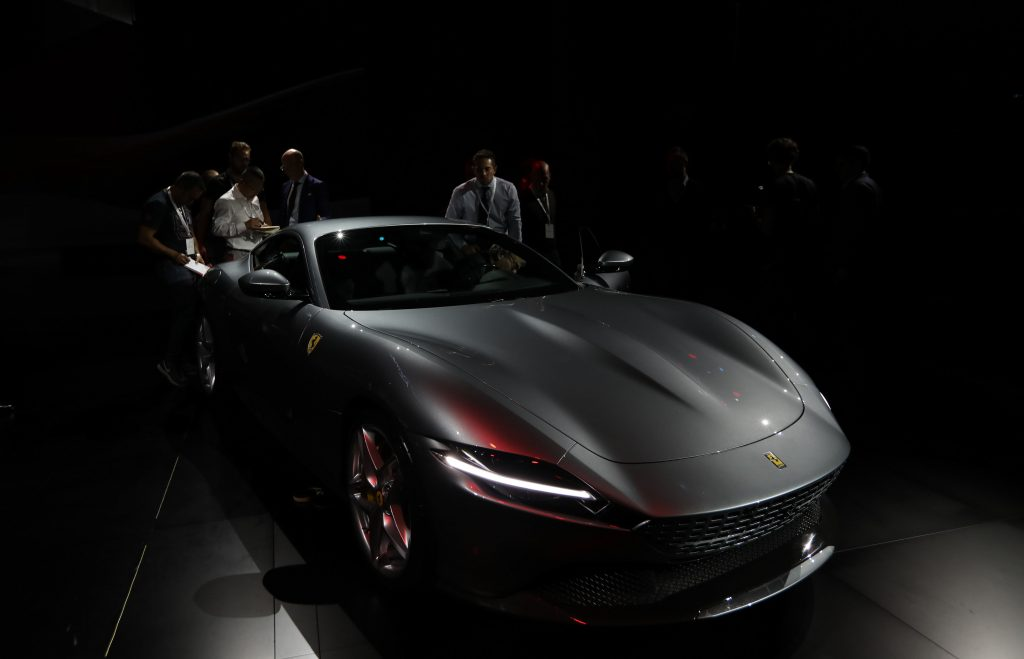 A grey Ferrari Roma, presumably sans CarPlay, shown on stage at it's reveal in Rome.