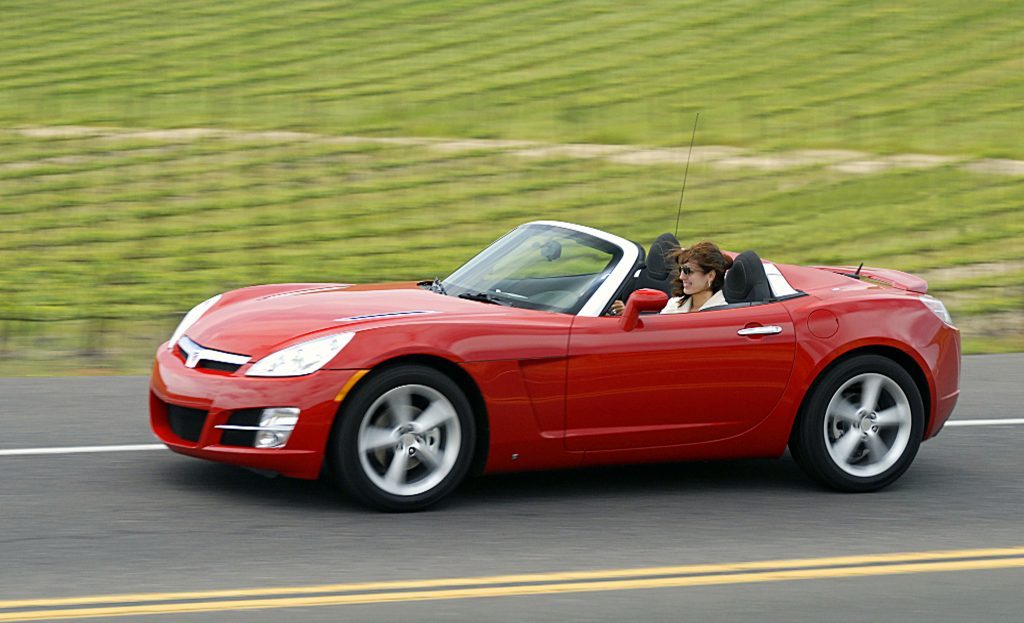A red saturn sky convertible with the top down driving down the highway