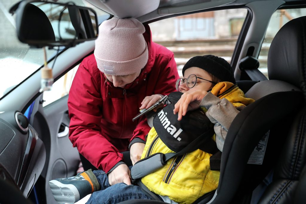 A mother buckles her son into the car