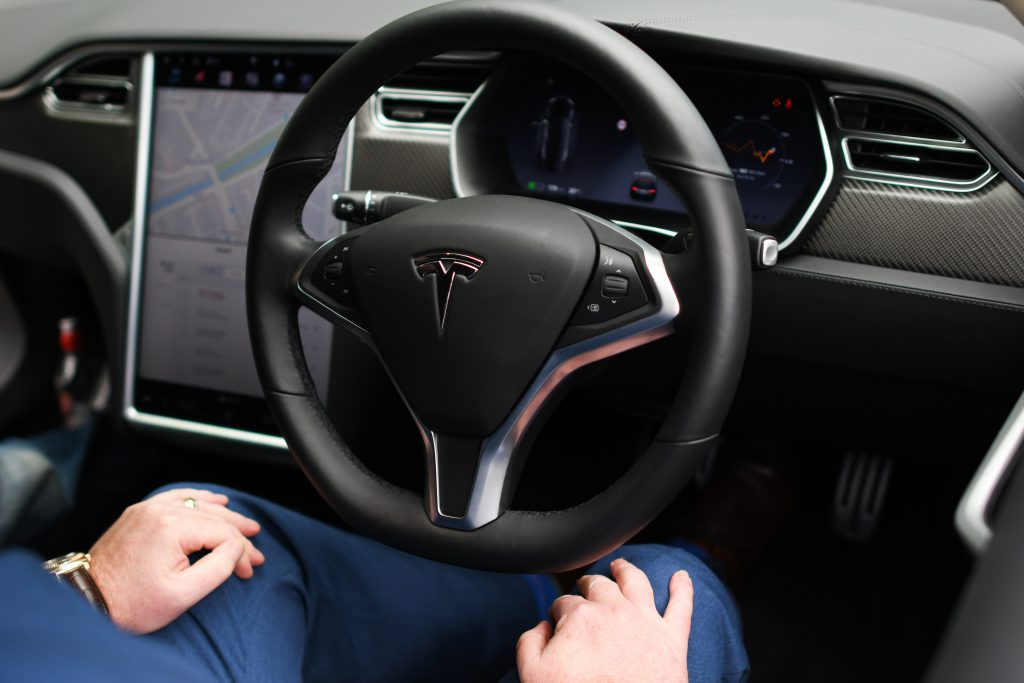 A driver rests their hands on their knees as the Tesla Model S they sit in drives itself autonomously.