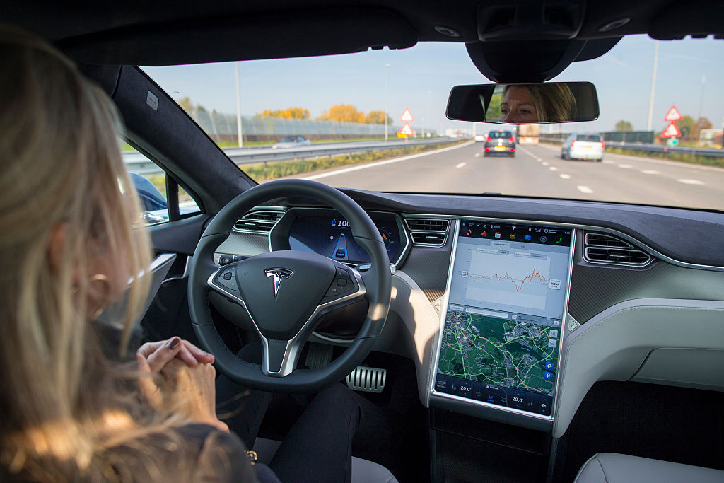 A woman sits in the driver seat of a Tesla, hands off the wheel, while autopilot guides the car down a road