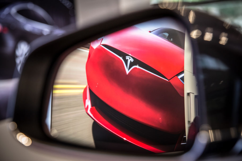 A red Tesla is shown approaching through another car's wing mirror