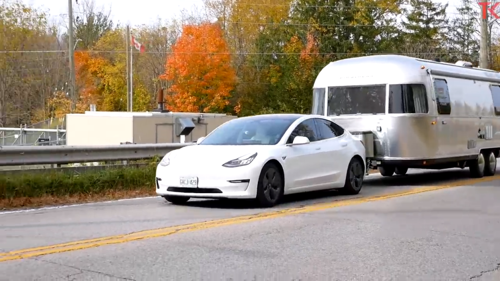 A shot of a Tesla Model 3 Towing an airstream trailer