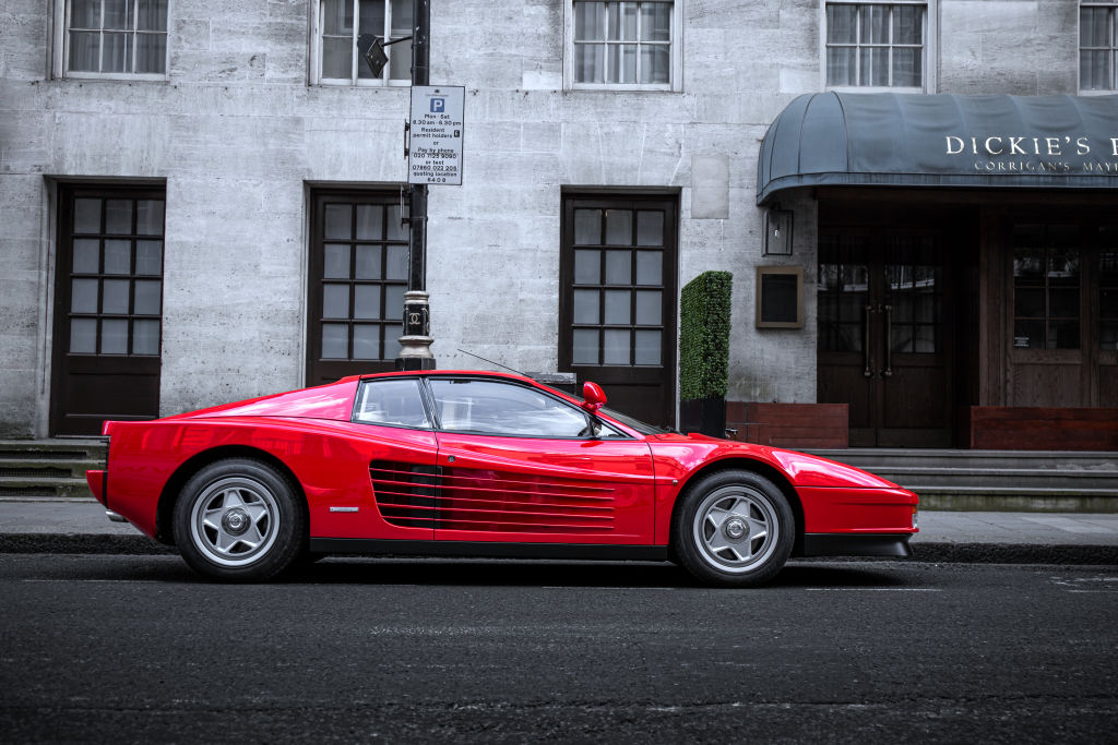 A red Ferrari Testarossa sits outside on a street in London, photographed in profile