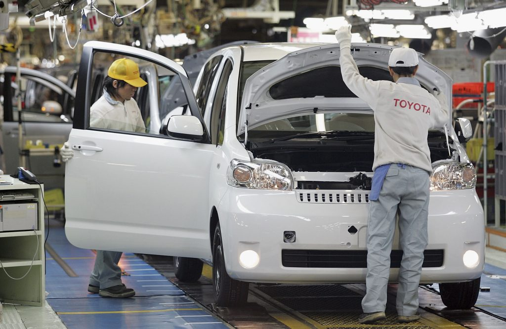 Toyota employees assemble a vehicle on the production line
