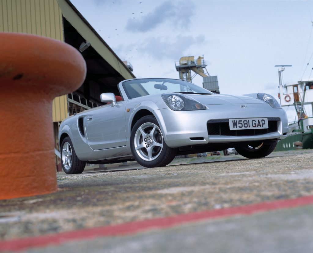 A silver toyota mr2 spyder with the convertible top down