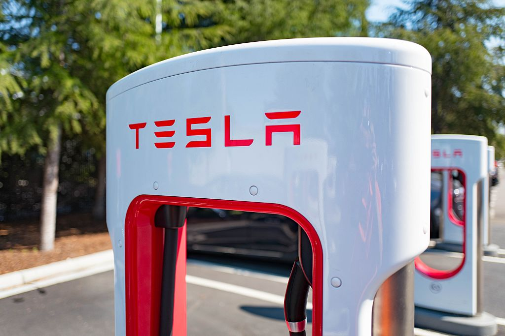 A white Tesla EV supercharger with red lettering sits in the sun