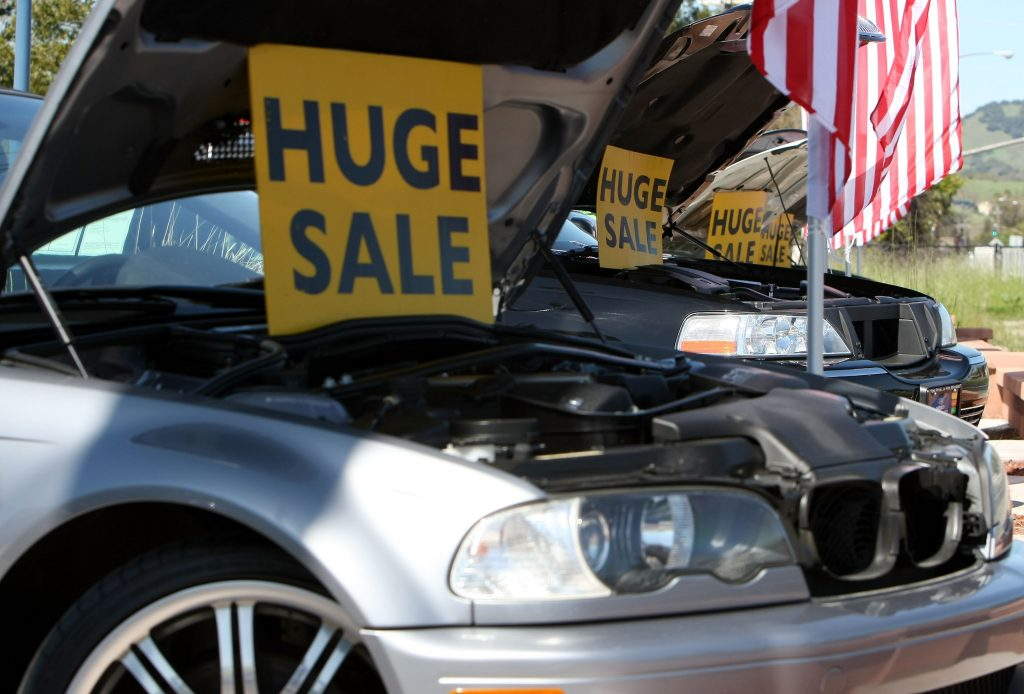 Signs advertising sales, propped up under the hoods of used cars