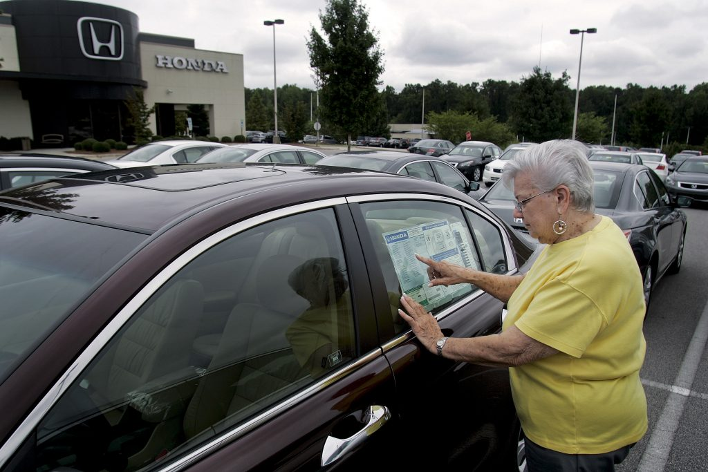 A woman with short silver hair in a yellow tee shirt examines the window sticker of a maron sedan on a sales lot
