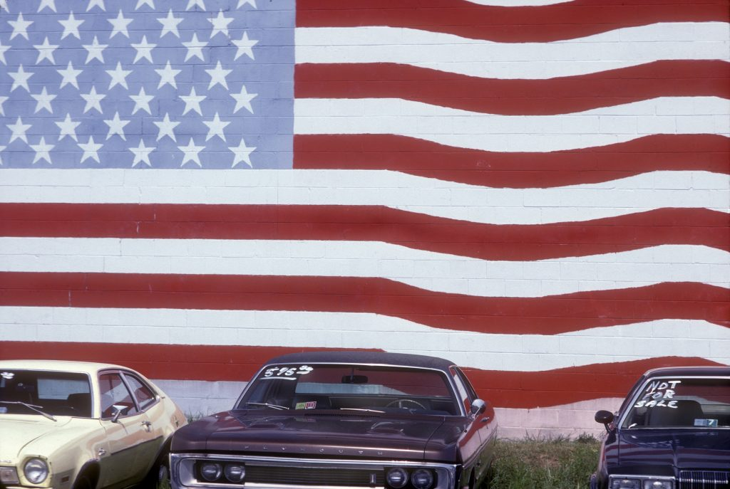 Used cars for sale in front of a wall painted with an American flag mural